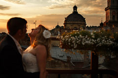 A wedding couple stands on the roof with great architecture behi Royalty Free Stock Photography