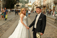 Wedding couple stands on the tramways somewhere in an old part o. F the city Royalty Free Stock Photo