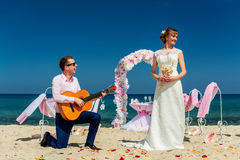 A wedding couple on a sunny beach. Fiance is playing a guitar song for his bride at a wedding ceremony on a sunny beach royalty free stock images