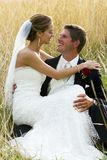 Wedding couple in tall grass outside. A happy young couple sitting in tall grass on their wedding day Stock Photo