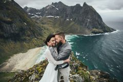 Wedding couple travelers on a hill in Norway, Kvalvika. Beautiful view of the beach, Lofoten, Norway. stock images