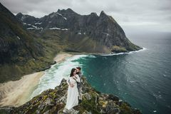 Wedding couple travelers on a hill in Norway, Kvalvika. Beautiful view of the beach, Lofoten, Norway. royalty free stock photo