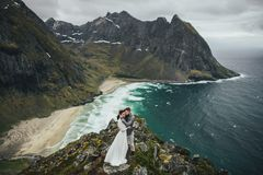 Wedding couple travelers on a hill in Norway, Kvalvika. Beautiful view of the beach, Lofoten, Norway. royalty free stock photos