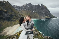 Wedding couple travelers on a hill in Norway, Kvalvika. Beautiful view of the beach, Lofoten, Norway. royalty free stock image