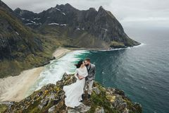 Wedding couple travelers on a hill in Norway, Kvalvika. Beautiful view of the beach, Lofoten, Norway. royalty free stock photography
