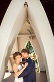 Wedding couple under architectural arch. Wedding couple standing under architectural stone arch Stock Photo