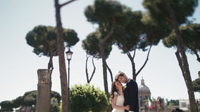 Wedding couple under clear blue sky at public plaza in Rome, Italy. Stylish groom kissing with beautiful bride stock video
