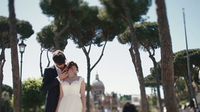 Wedding couple under clear blue sky at public plaza in Rome, Italy. Stylish groom tendelrly kissing with beautiful bride stock footage
