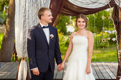 Wedding couple under wedding arch in summer. Beautiful wedding couple under wedding arch in summer Stock Image