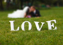 Wedding couple unfocused and love word on the grass. Wedding couple unfocused and big white love word on the grass Stock Photos