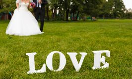Wedding couple unfocused and love word on the grass Stock Photography