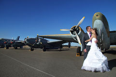 Wedding couple with vintage airplanes. Married couple, groom kissing bride romantic moment, with vintage military airplanes, clear blue skies next to runway royalty free stock image