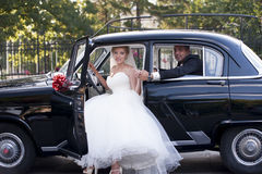 Wedding couple with a vintage car royalty free stock image