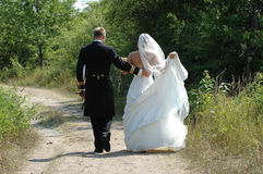 Wedding couple walking. A wedding couple walking togeter Stock Photos