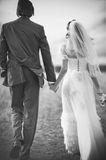 Wedding couple walking. Young wedding couple walking on field. Retro style black and white colors Royalty Free Stock Images