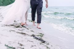Wedding couple walking barefoot on the sand beach. Cropped royalty free stock images