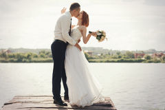 Wedding couple walking on bridge near lake on sunset at wedding day. Bride and groom in love Stock Photos