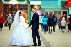 Wedding couple walking crowded city street Stock Images