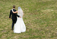 Wedding Couple walking on gras Royalty Free Stock Photos