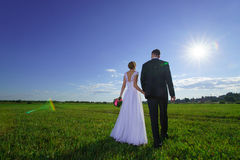 Wedding couple walking through green field Royalty Free Stock Photo