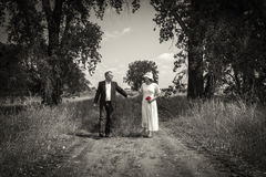 Wedding couple walking hand in hand down a country path. Stock Photo