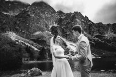Wedding couple walking and holding hands on the lake shore. Sunny day in Tatra mountains. Black and white stock image