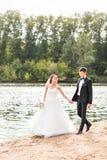 Wedding couple walking  near lake. Royalty Free Stock Images