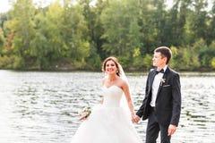 Wedding couple walking near lake. Bride and groom standing and kissing near lake stock photos