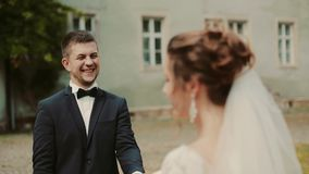 Wedding couple walking in the park with historic palace. Brunette young stylish woman bride first meeting groom stock footage
