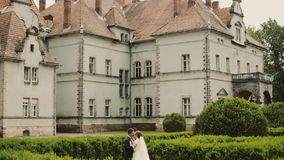 Wedding couple walking in the park with historic palace. Brunette young stylish woman bride first meeting groom stock video