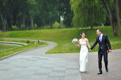 Wedding couple walking in a park together Stock Photo