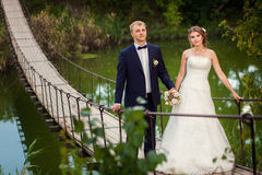 Wedding couple walking on suspension bridge Stock Images
