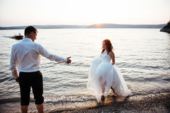 Wedding couple in the water at sunset Stock Photo