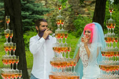 Free Wedding Couple With Pyramids Of Wine Glasses Outdoor Stock Photo - 74547870