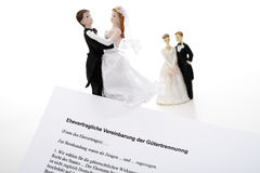Wedding couples figurines behind magisterial form sheet Stock Photos