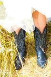 Wedding Cowboy Boots. A bride wearing her black and blue cowboy (or cowgirl) boots on her wedding day royalty free stock image