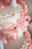 Wedding cream pink cake. Wedding cream cake,pink bows, flowers and bow, detail Royalty Free Stock Photo
