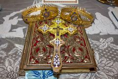 Wedding crowns and bible. Wedding crowns and cross on bible in orthodox church royalty free stock photography