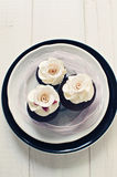 Wedding cupcake with delicate white fondant roses. Delicate and elegant wedding chocolate cupcakes with white frosting and fondant roses with pink ribbon Royalty Free Stock Photography