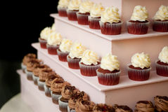 Wedding Cupcake Tower. Tiers of frosted wedding cupcakes resting on a pink tower Stock Photos