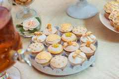 Wedding Cupcakes delicate shades. Wedding cupcakes with butter-cream frosting in gold cupcake liners Royalty Free Stock Image