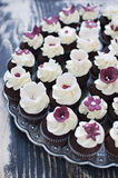 Wedding cupcakes with fondant flower decorations. Delicate and elegant wedding chocolate cupcakes with white frosting and fondant flower and butterfly Stock Photos