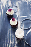 Wedding cupcakes with fondant flower decorations. Delicate and elegant wedding chocolate cupcakes with white frosting and fondant flower decorations and silver Royalty Free Stock Images
