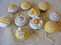 Wedding cupcakeswith fondant angels, roses, camea, flowers and jewellery beads. Wedding yellow cupcakeswith fondant angels, roses, camea, flowers and jewellery stock photos