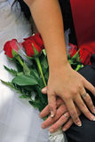 Wedding Day. Crossed hands with ring and roses on wedding day stock images