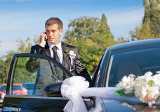 Wedding Day. The groom speaks by phone near dressed up the wedding car Stock Image