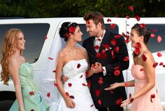 Wedding day. Bridesmaids throwing rose petals on young couple stock image
