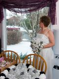 Wedding Day. A middle aged bride stares out the window in anticipation of her wedding royalty free stock photography