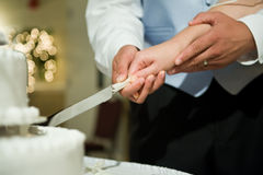 Wedding day. The groom and the bride cut a wedding cake together Stock Photo