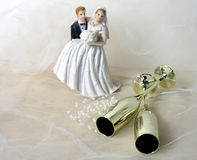 Wedding Day. Bride and groom figurine, 2 gold champagne flutes, white beads on white netting stock image